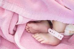 Le pied de plan rapproché du bébé avec l'étiquette nouveau-née de cheville sur le lit dans l'hôpital a donné au fond une consista photos stock