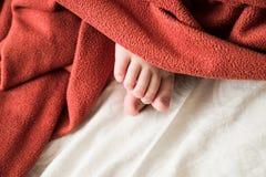 Le pied du bébé sous une couverture Image libre de droits