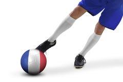 Le pied du joueur de football donne un coup de pied une boule Image stock