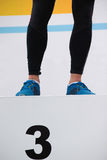 Le pied du ` s d'athlète sont sur le support de médailles ; Troisième endroit Image libre de droits