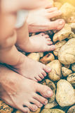 Le pied du ` s d'enfant apprend à marcher sur des cailloux avec le père ensemble sur s Photo libre de droits