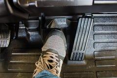 Le pied du ` s de conducteur à l'étape sur la pédale de freinage image stock