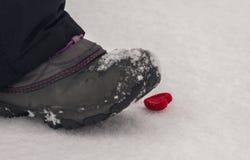 Le pied frappe du pied coeur dans la neige Amour malheureux Photos libres de droits