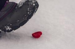 Le pied frappe du pied coeur dans la neige Amour malheureux Photo stock