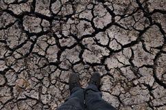 Le pied humain est la terre criquée Image stock
