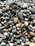 Le pietre bagnate del mare ai precedenti della spiaggia Fotografia Stock