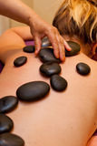 Le pietre calde hanno allineato sulla parte posteriore della giovane donna per il massaggio Immagine Stock