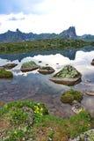Le pietre contro lo sfondo del cielo hanno riflesso nel lago Immagine Stock