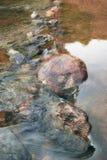 Le pietre del granito sul fondo dello scorrimento dell'acqua di una montagna raffreddano la corrente fotografia stock