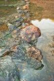 Le pietre del granito sul fondo dello scorrimento dell'acqua di una montagna raffreddano la corrente immagini stock