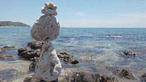 Le pietre di zen equilibrano al fondo pietroso del mare e della spiaggia video d archivio