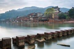 Le pietre facenti un passo attraverso il fiume di Tuojiang con il portone del nord si elevano nei precedenti in Fenghuang, la pro Immagine Stock