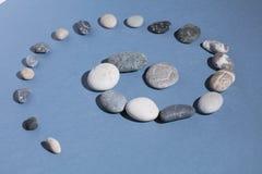 Le pietre grige e bianche si sviluppano a spirale sui precedenti blu immagine stock