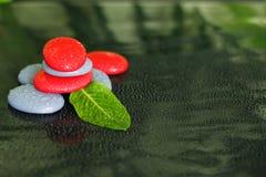 Le pietre grige e rosse con le gocce dell'acqua e di una foglia verde hanno sistemato nello stile di vita di zen su fondo nero Immagine Stock
