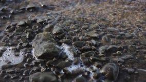 Le pietre sono lavate dall'acqua di fiume, schiuma calma della forma di onde stock footage