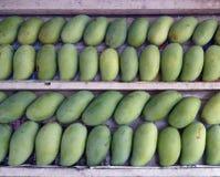 Le pile di manghi verdi maturi dell'aroma dolce fruttificano sulla pila di legno Immagini Stock
