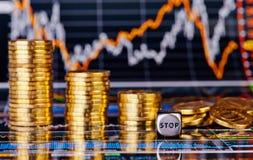 Le pile dorate delle monete di tendenza al ribasso, taglia il cubo a cubetti con la parola FERMATA Immagini Stock Libere da Diritti