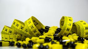 Le pillole con nastro adesivo di misurazione su fondo bianco, rappresentano l'industria della pillola di dieta immagini stock