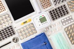 Le pillole dalla macchina di pressione sanguigna con il computer della compressa e sfrega Immagini Stock Libere da Diritti