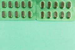 Le pillole di erbe verdi della compressa produce delle bolle su sul piano di appoggio medico Fotografie Stock
