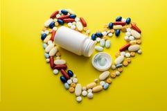 Le pillole e le capsule nel cuore modellano con la bottiglia Fotografia Stock