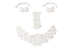 Le pillole hanno organizzato nella figura del fronte fotografie stock libere da diritti