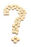 Le pillole hanno organizzato nella figura del punto interrogativo fotografia stock