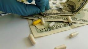 Le pillole incapsula i dollari di caduta, mano, concetto del guanto stock footage
