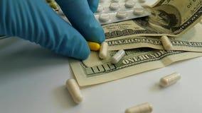 Le pillole incapsula la mano di caduta del dollaro, concetto del guanto stock footage