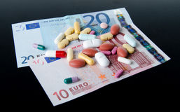 Le pillole, le compresse e le capsule si sono sparse sulle banconote Fotografia Stock