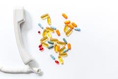 Le pillole Multicoloured con il microtelefono del telefono sulla vista superiore del fondo bianco chiamano medico fotografie stock