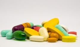 Le pillole poste sopra i precedenti bianchi fotografie stock