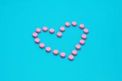 Le pillole rosa nel cuore modellano su fondo blu Fotografia Stock