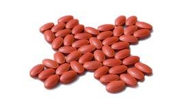Le pillole rosse sono sistemate nel simbolo trasversale fotografia stock