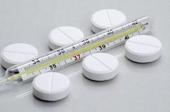 Le pillole si trovano accanto al termometro medico fotografia stock