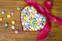 Le pillole variopinte del cioccolato in un cuore hanno modellato la scatola Immagine Stock