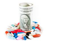 Le pillole variopinte si avvicinano ai dollari acciambellati su fondo bianco Fotografie Stock