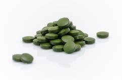 Le pillole verdi dell'alga della clorella di spirulina si chiudono su su bianco Fotografie Stock Libere da Diritti