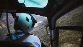 Le pilote dans le vol de carlingue d'hélicoptère en montagnes banque de vidéos