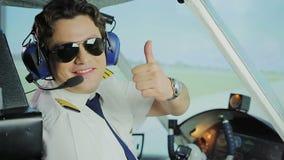 Le pilote masculin heureux dans des lunettes de soleil souriant à l'appareil-photo, faisant manie maladroitement vers le haut du  banque de vidéos
