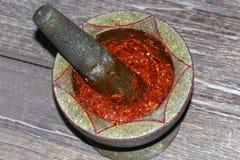 Le piment rectifiant dans la pierre de mortier sur le fond, le mortier et le pilon en bois est meulage rouge et ail de piment pou photographie stock libre de droits