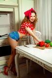 Le Pin vers le haut de la femme au foyer de style posant dans la cuisine et souriant dessus est venu Photos stock