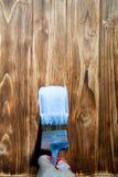Le pinceau et la cuvette de couleur blanche de revêtement ont mis dessus le conseil en bois Image libre de droits