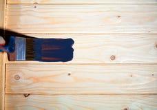 Le pinceau et la cuvette de couleur blanche de revêtement ont mis dessus le conseil en bois Photo libre de droits