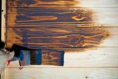 Le pinceau et la cuvette de couleur blanche de revêtement ont mis dessus le conseil en bois Photo stock