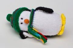 Le pingouin a bourré le jouet sur le fond blanc se couchant sur le blanc Photo stock