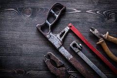 Le pinze d'annata obsolete del tagliafili della sega a mano sul bordo di legno cons Fotografie Stock Libere da Diritti