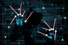 Le pirate informatique à capuchon change le programme informatique sur un écran tactile avec deux Photo libre de droits