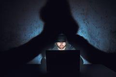 Le pirate informatique d'homme travaille dans la pièce vide sombre photos stock