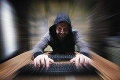 Le pirate informatique dans le capot s'assied et travaille images stock